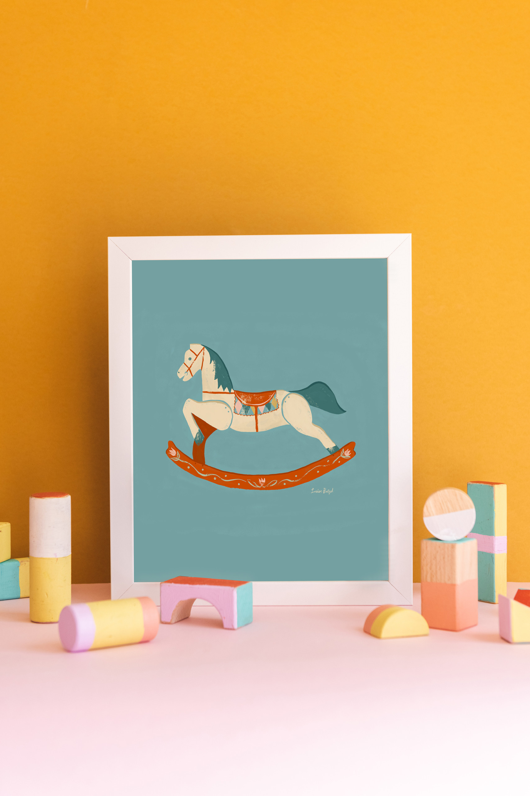 A print of Louise Pretzel's Rocking Horse leaning against a gold wall with pastel wooden blocks in front of it.