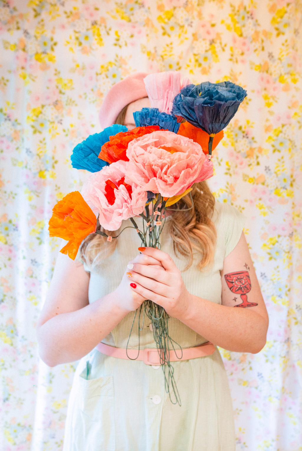Louise Pretzel stands against a floral backdrop wearing a pink beret and a dress. She's holding paper flowers in front of her face.