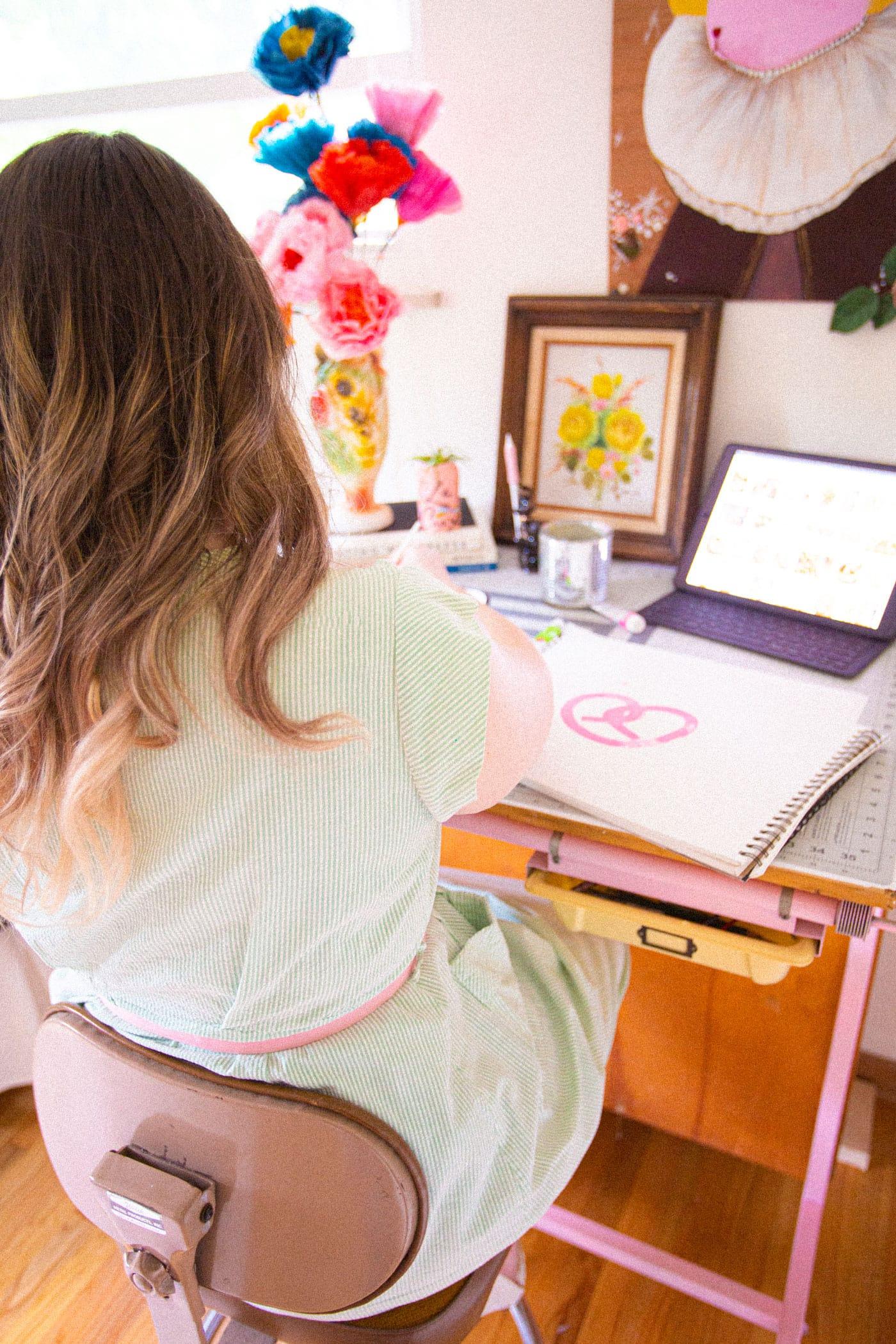 Louise sits at a desk painting a pink pretzel.