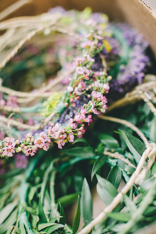 waxflower and laurel flower crowns are stacked in a pile.