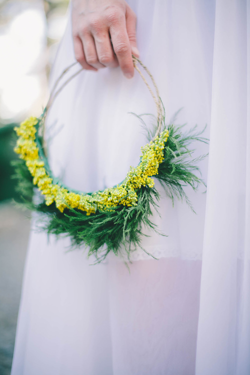Goldenrod flower crown from Midsummer Mingle. A woman in a white dress holds it against her side.