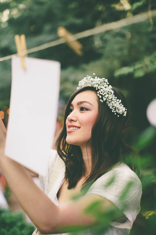 A woman in white wearing a white floral crown hangs up a picture on a clothesline
