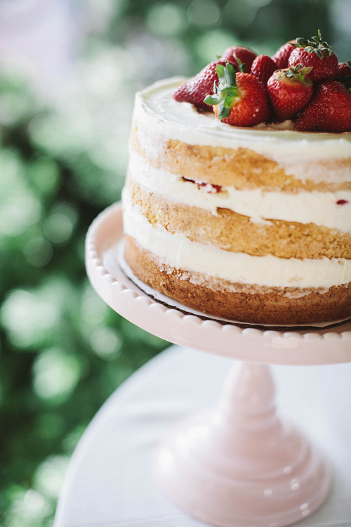 strawberry-covered layer cakes on pastel cakestands at an outdoor party