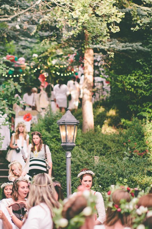 Women dressed in white descend stairs in a green space filled with dappled light.