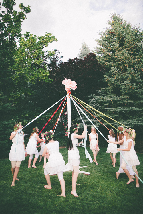 Women in white dance around a maypole in a park filled with trees. It's dusk.