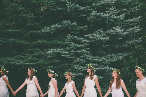 Women in white wearing flower crowns hold hands and walk in a line in front of some pine trees.