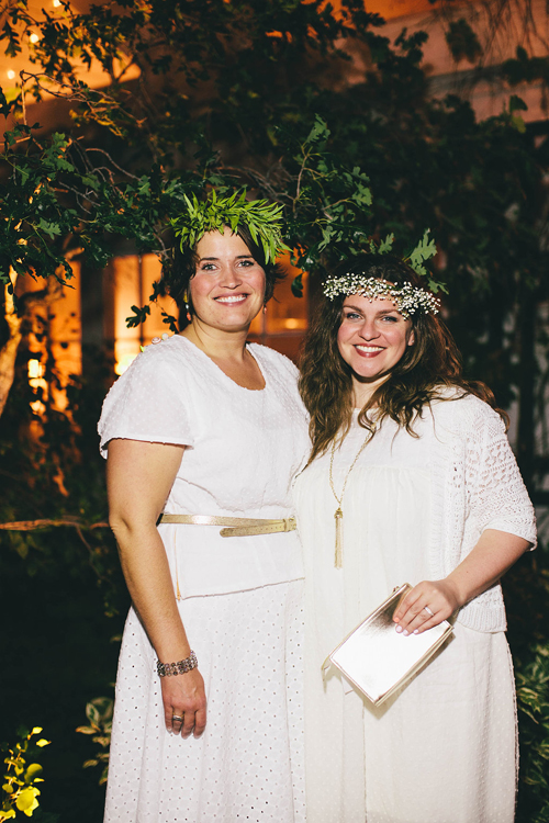 Two women in white wearing floral crowns smile at the camera. It's night and the background is distantly lit with warm light.