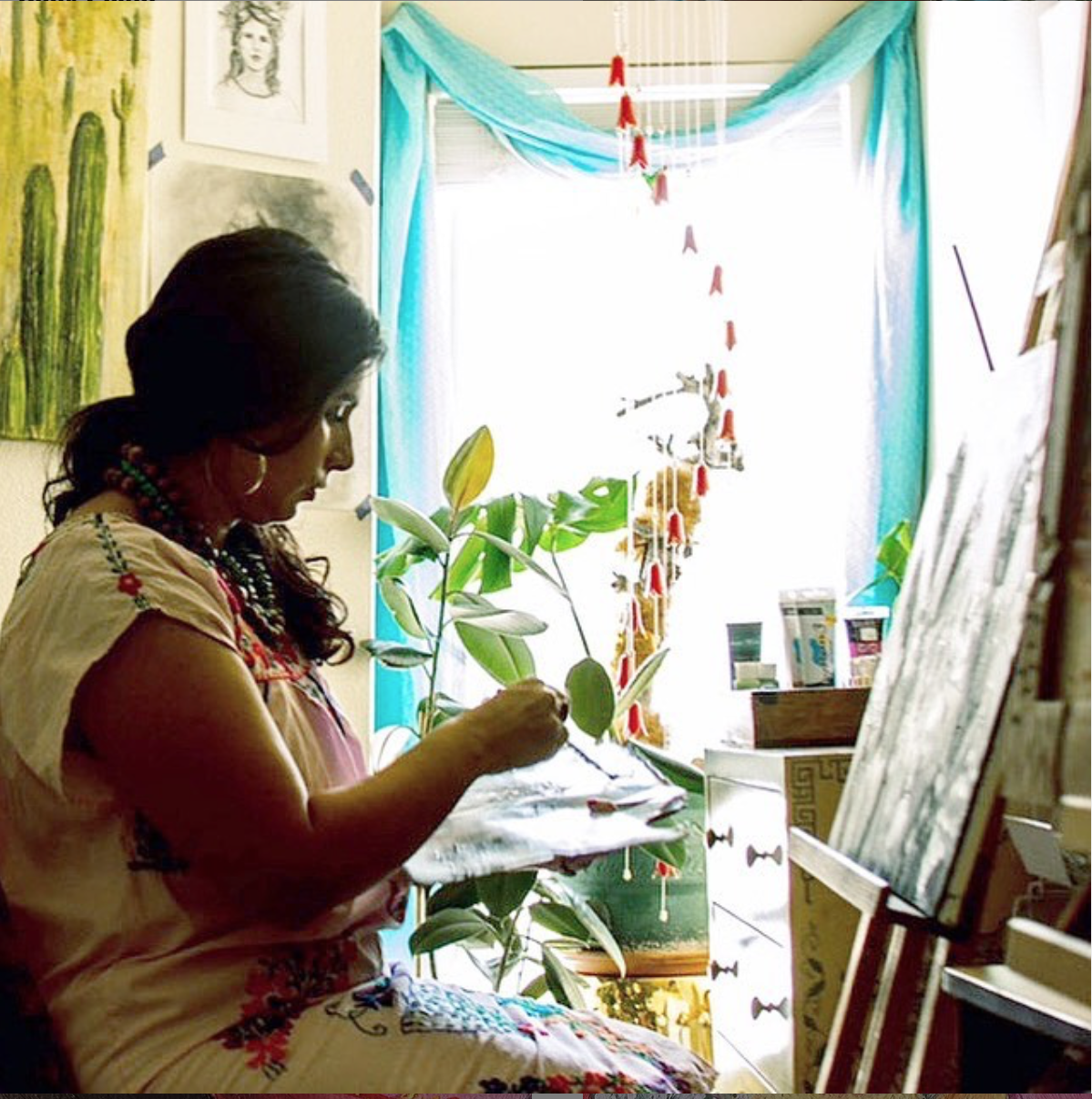 Michelle paints in a light filled room with plants around her.