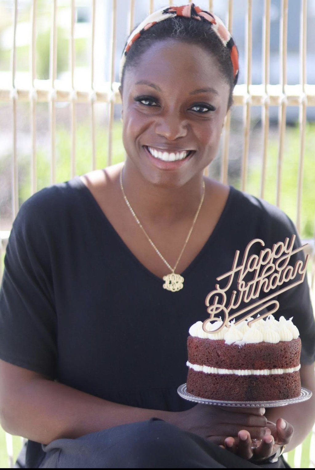 Sheryl Garner holds a red velvet cake and smiles at the camera. She's wearing a black top and a gold necklace.