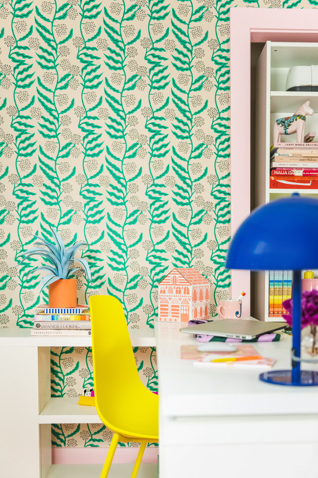 A brightly colored office. There's green floral wallpaper, a yellow chair, white tables and shelves, pink-painted doorframes, a blue modern lamp, an orange paper house, ad office supplies.