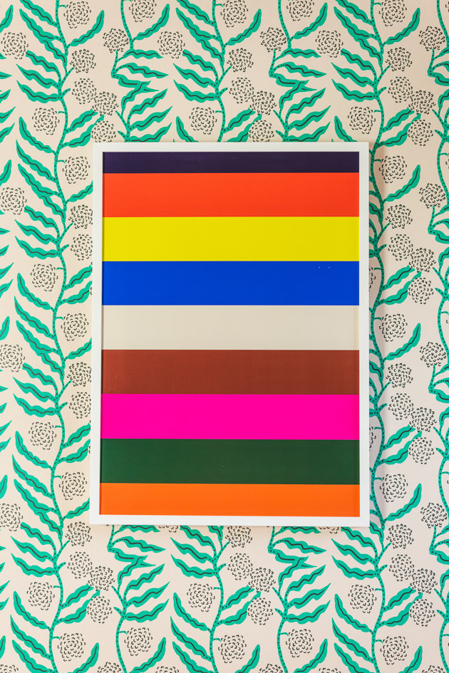 a horizontally striped art print hanging on a wallpapered wall. The wallpaper is a modern green botanical pattern.