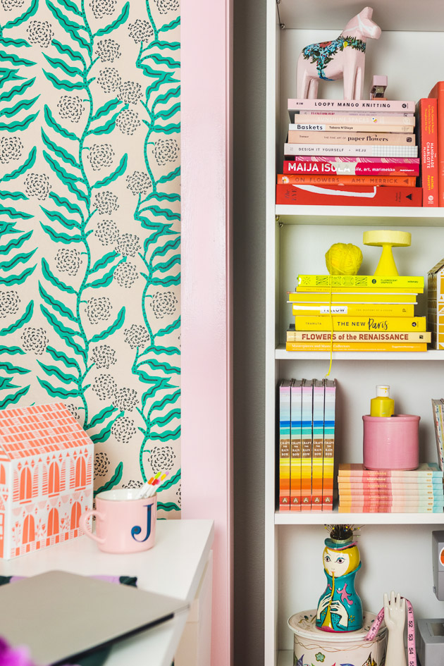Shot of the finished office. On the left is the wallpaper and a corner of a desk with an orange paper house. Then theres a pink painted door frame, then a bookshelf full of rainbow books and objects.