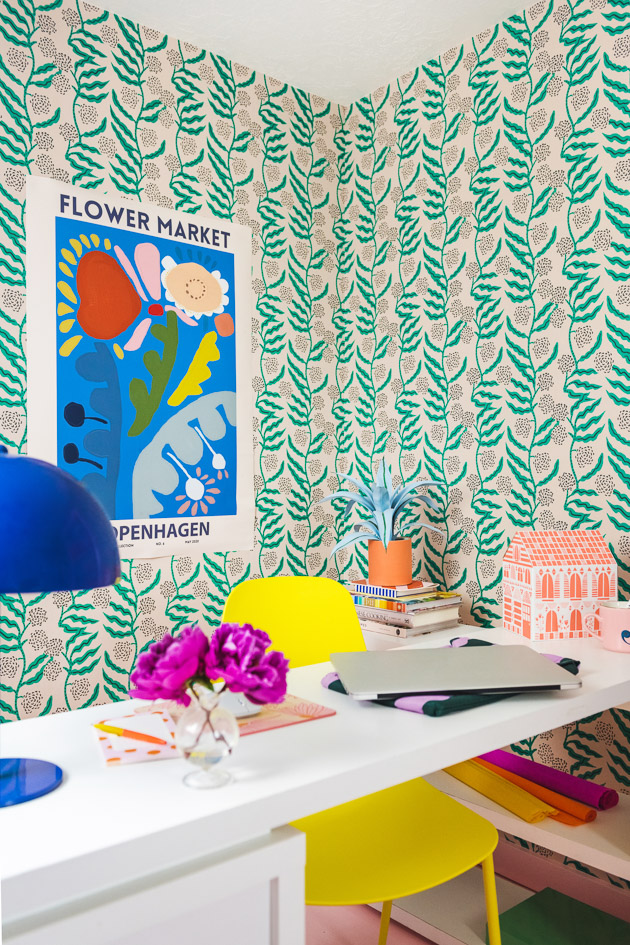 A brightly colored office. There's green floral wallpaper, a pink floor, a yellow chair, a white table, an orange paper house, a blue poster with colorful abstract flowers, and office supplies.