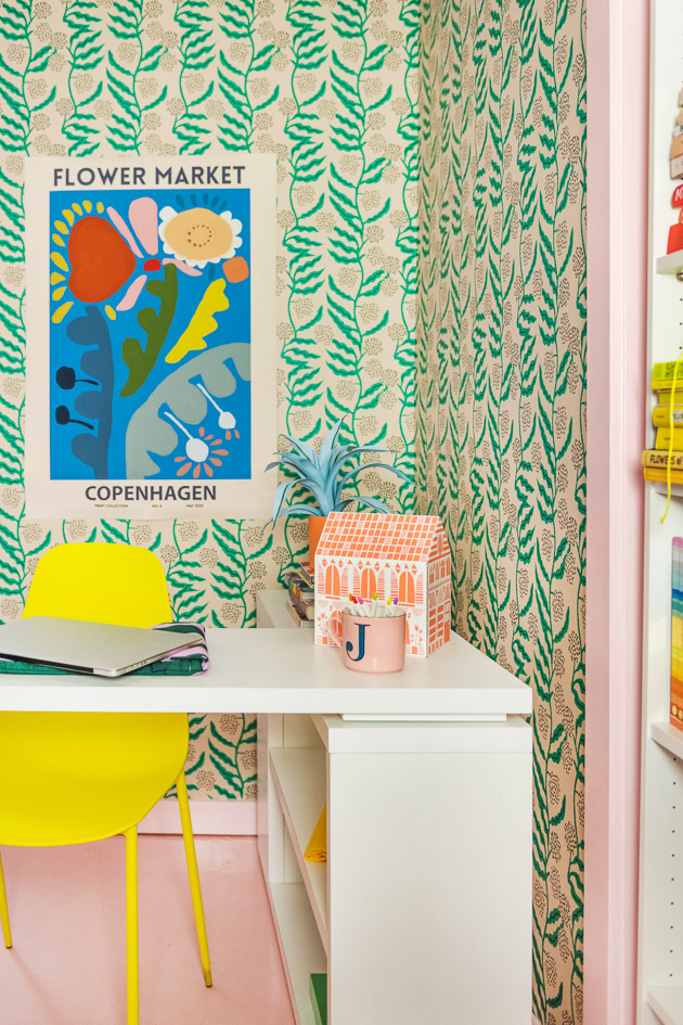 A brightly colored office. There's green floral wallpaper, a pink floor, a yellow chair, a white table, pink-painted doorframes, an orange paper house, a blue poster with colorful abstract flowers, and office supplies.