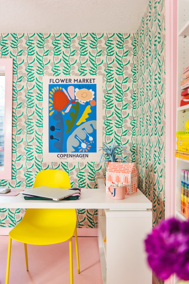 a blue poster with flowers drawn on it hangs on a green botanical wallpapered wall. There's a bright yellow chair, white office furniture, and a pink room in the space.