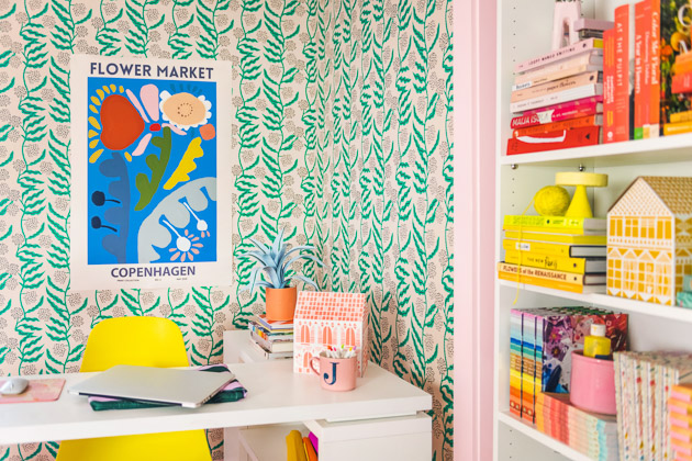 Interior shot of the finished office. You can see the wallpaper, the blue art print with colorful flowers, and the desk with an orange paper house and yellow chair, and you can also see a shelf installed in the closet that's filled with a rainbow of books.