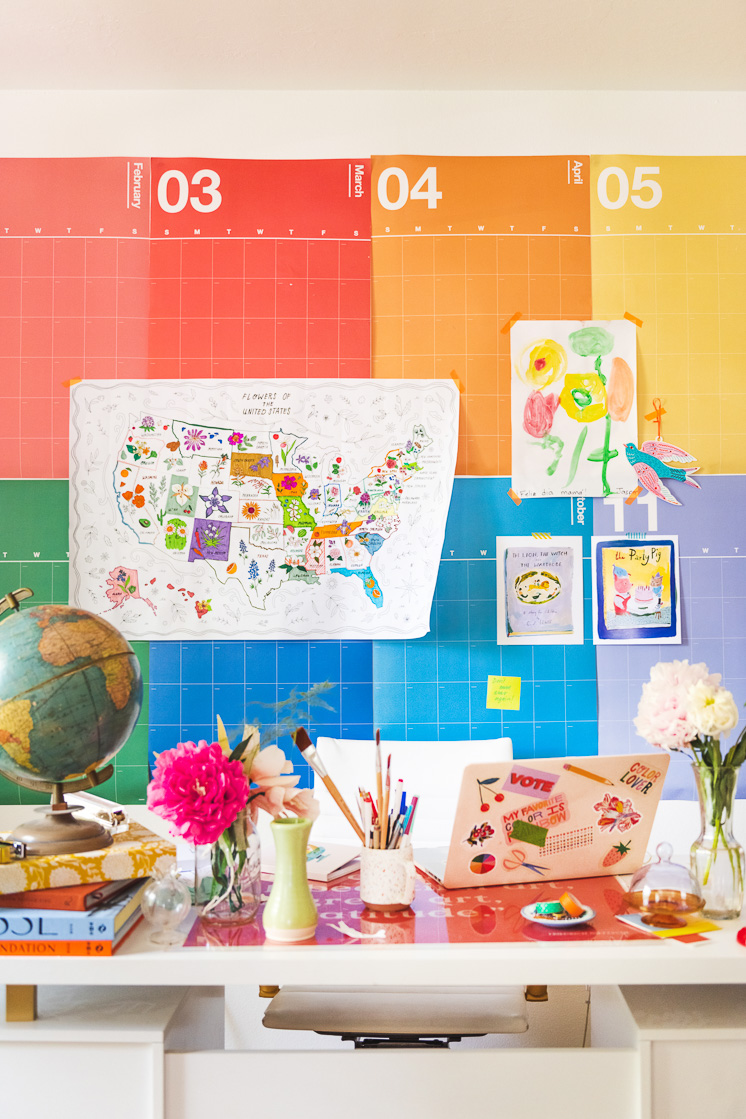 The State Flower Map Coloring Page hangs on Brittany's rainbow calendar with some art prints, a painting by Jasper, and a cutout bird. A colorful desk with flowers, a laptop, books, and a globe is in front of the calendar.