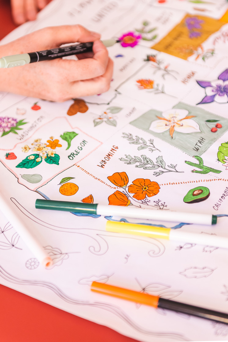 The coloring map is on a red table. Colorful markers are scattered around and some hands reach in to color it.