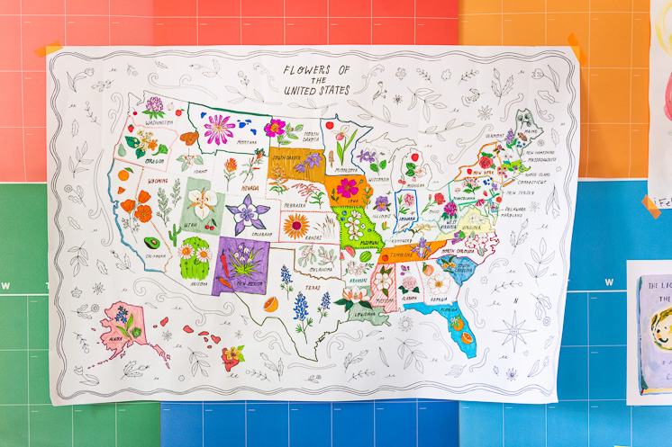 The State Flower Map Coloring Page hangs on Brittany's rainbow calendar with some art prints and a painting by Jasper.