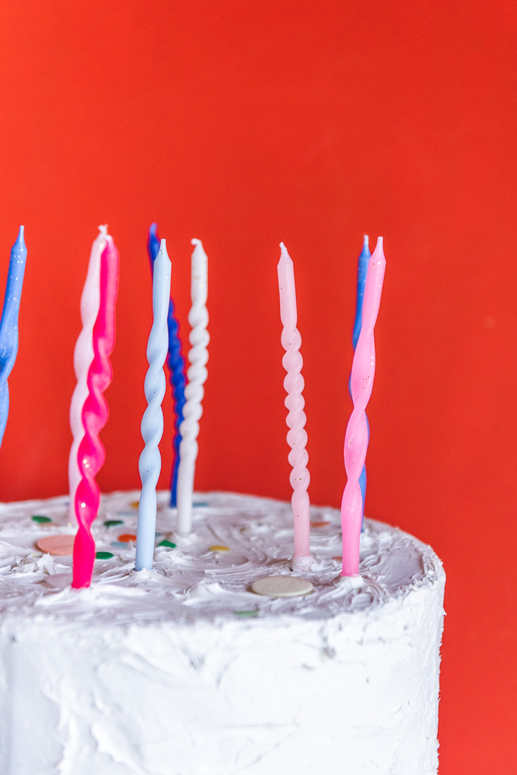 Close up of twisted birthday candles on a white cake with a red background.