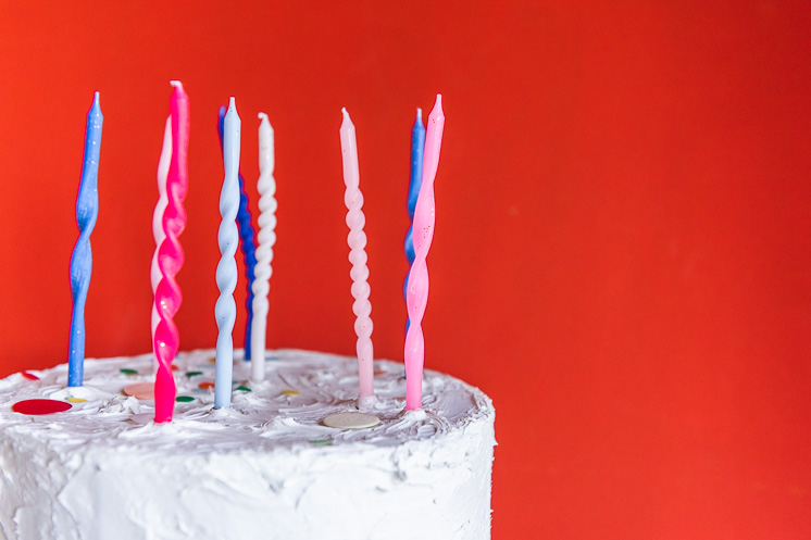 Twisted birthday candles on a white cake with a red background.