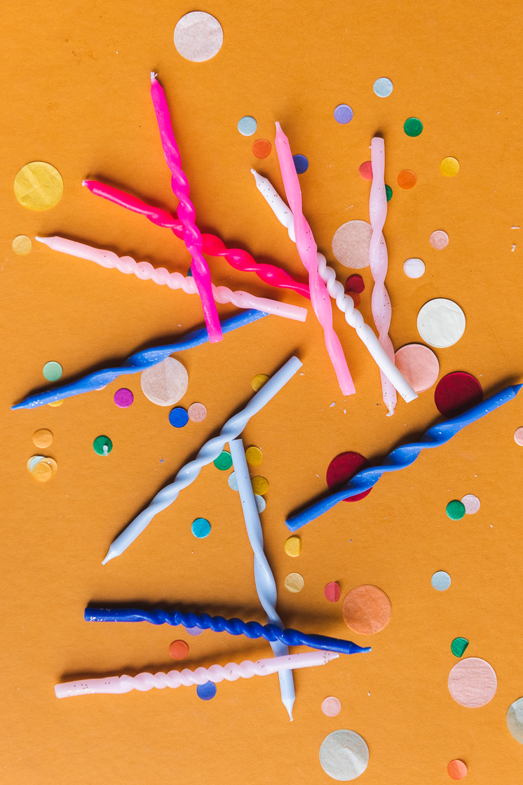 A flat lay of twisted birthday candles and confetti on an orange background.