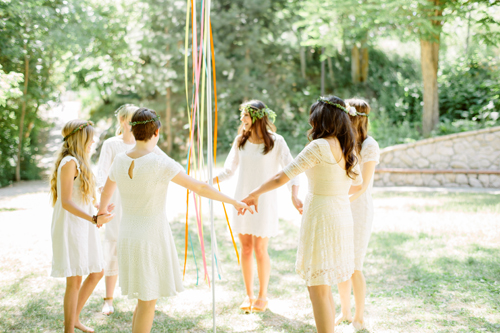 women dressed in white dance around a DIY maypole in a green park with dappled light.