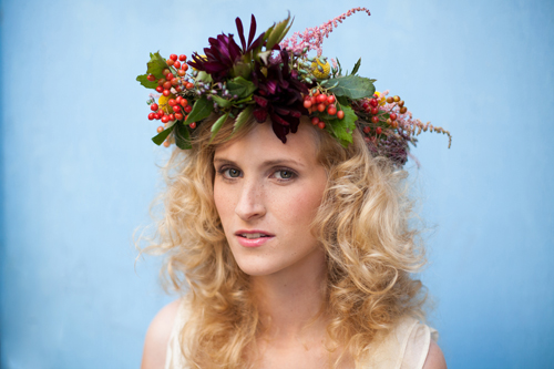 A woman wearing a lavish flower crown of dahlias and berries and greenery looks at the camera. The background is sky blue.