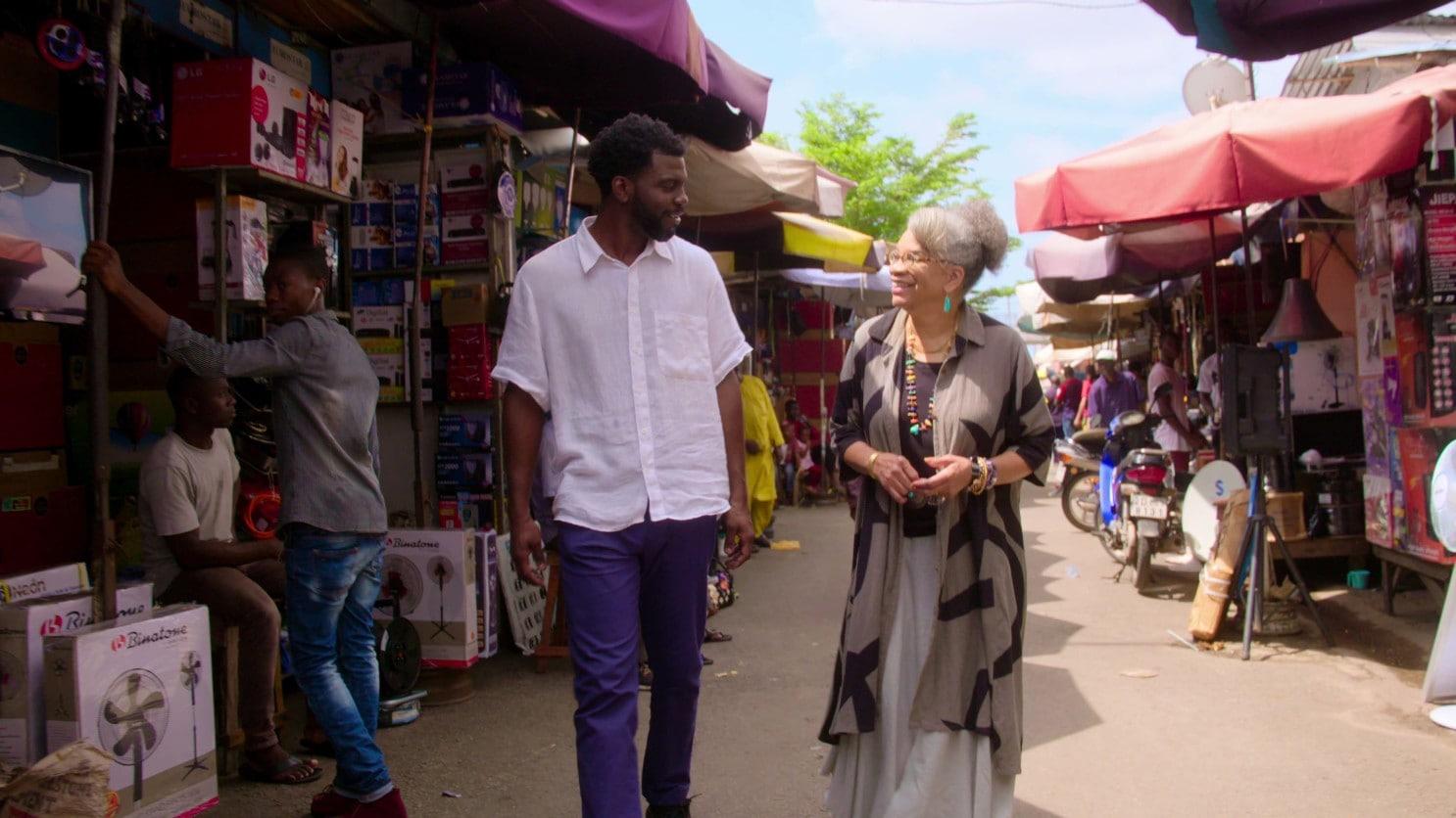 A tall Black man and a Black woman walk through a street market in Benin.