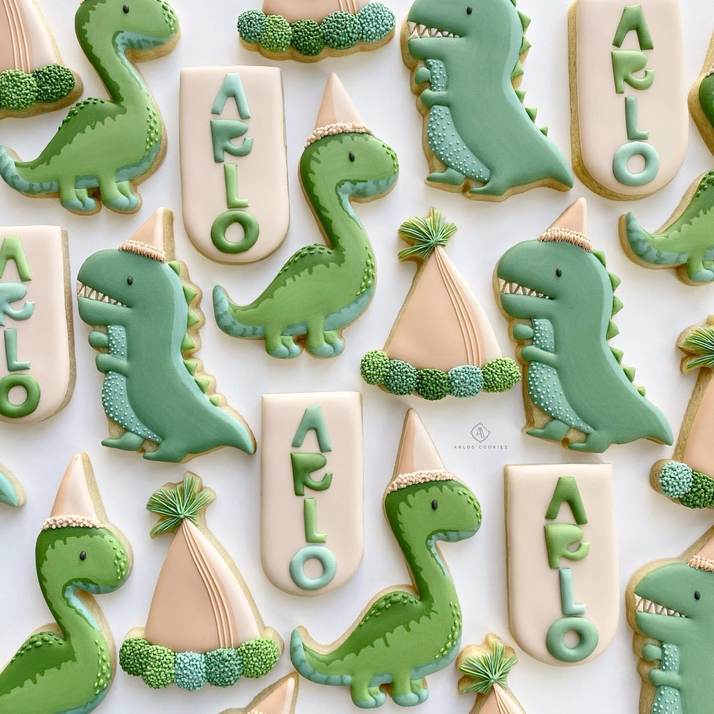 """Decorated cookies in the shapes of dinosaurs, party hats, and pendants with the name """"Arlo"""" arranged in a flat lay."""