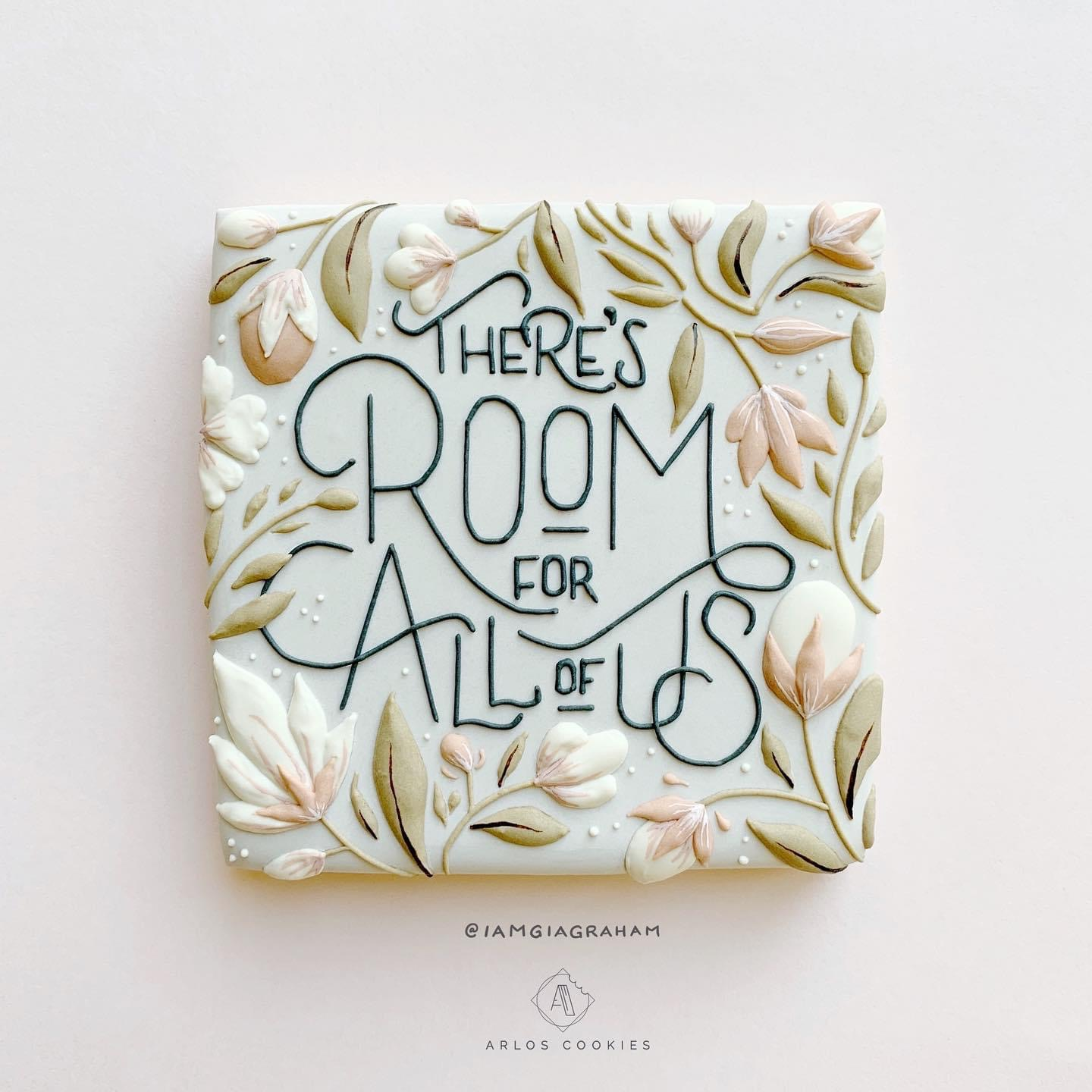 """A square cookie decorated with pink and green flowers and decorative text reading """"there's room for all of us"""""""