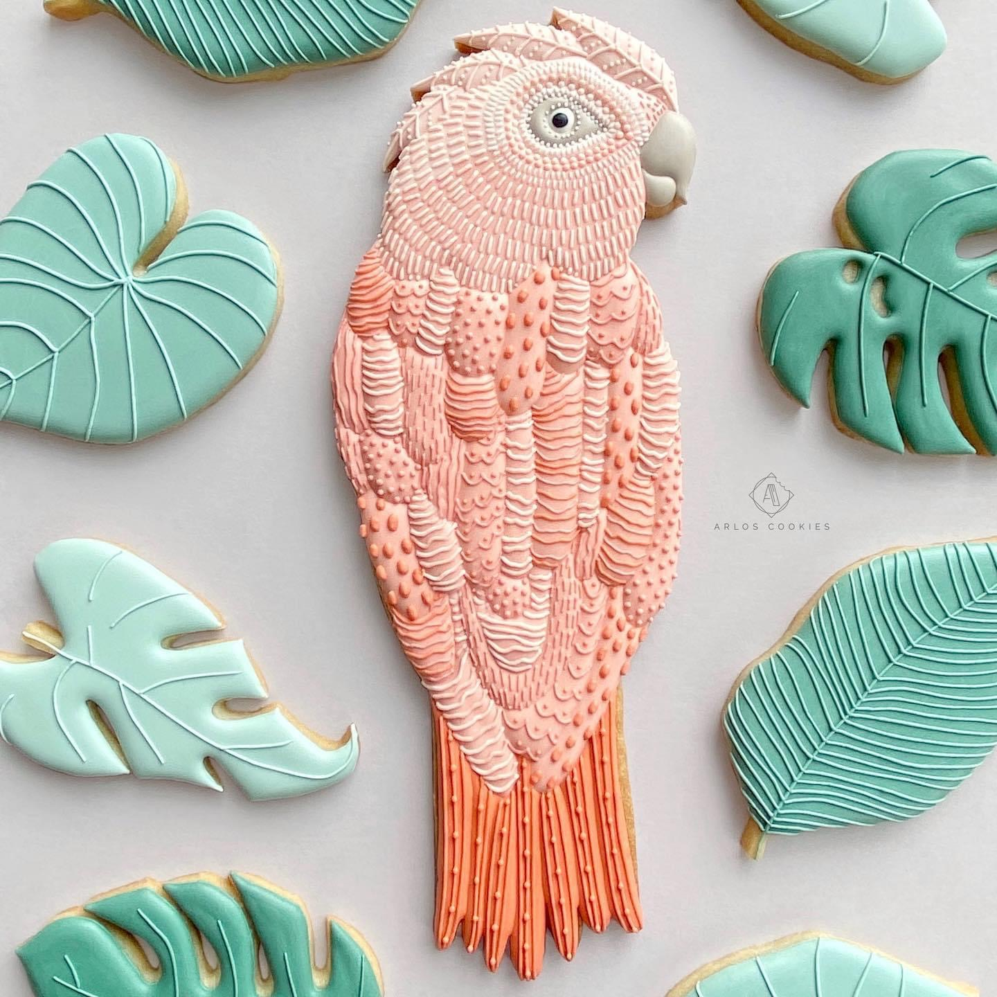 Decorated pink parrot cookie surrounded by green leaf cookies.
