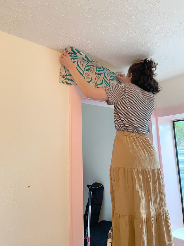 Hailey stands on a stepstool and installs the green vined wallpaper. She's wearing a striped t shirt and a tan skirt.