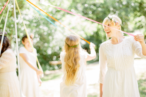 Brittany is wearing white and dancing around a DIY maypole with her interns, who are also wearing white.