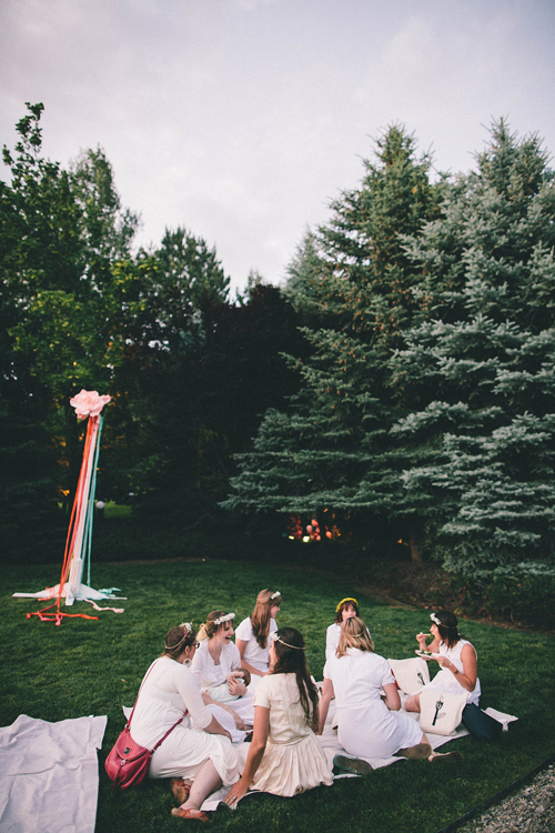 women dressed in white eat on a picnic blanket. In the background, a maypole stands in front of some pine trees. It's dusk.