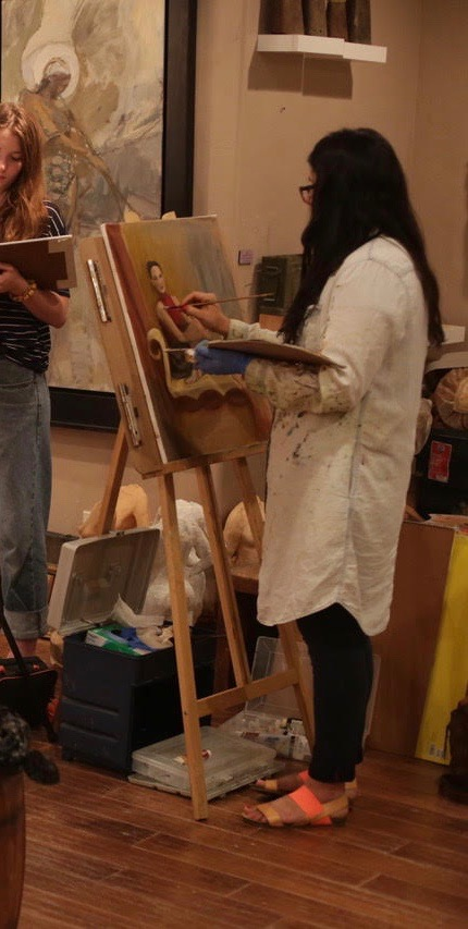 Michelle stands in a dim room painting at an easel.