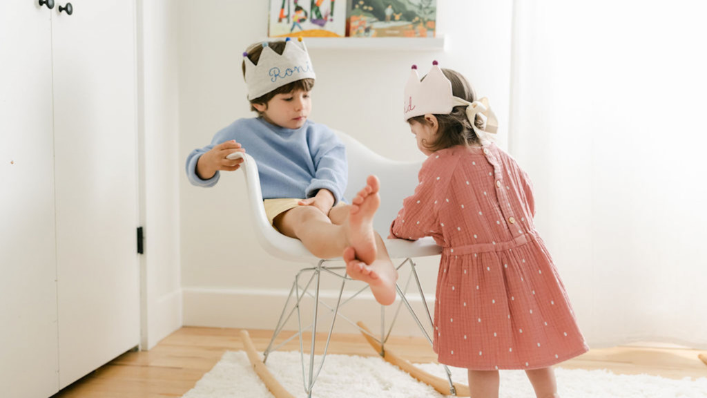 Two kids wearing linen birthday crowns and playing. A girl is wearing a pink dress and white crown, and a boy is wearing a blue sweater, yellow shorts, and a grey crown. They're in a light-filled room.