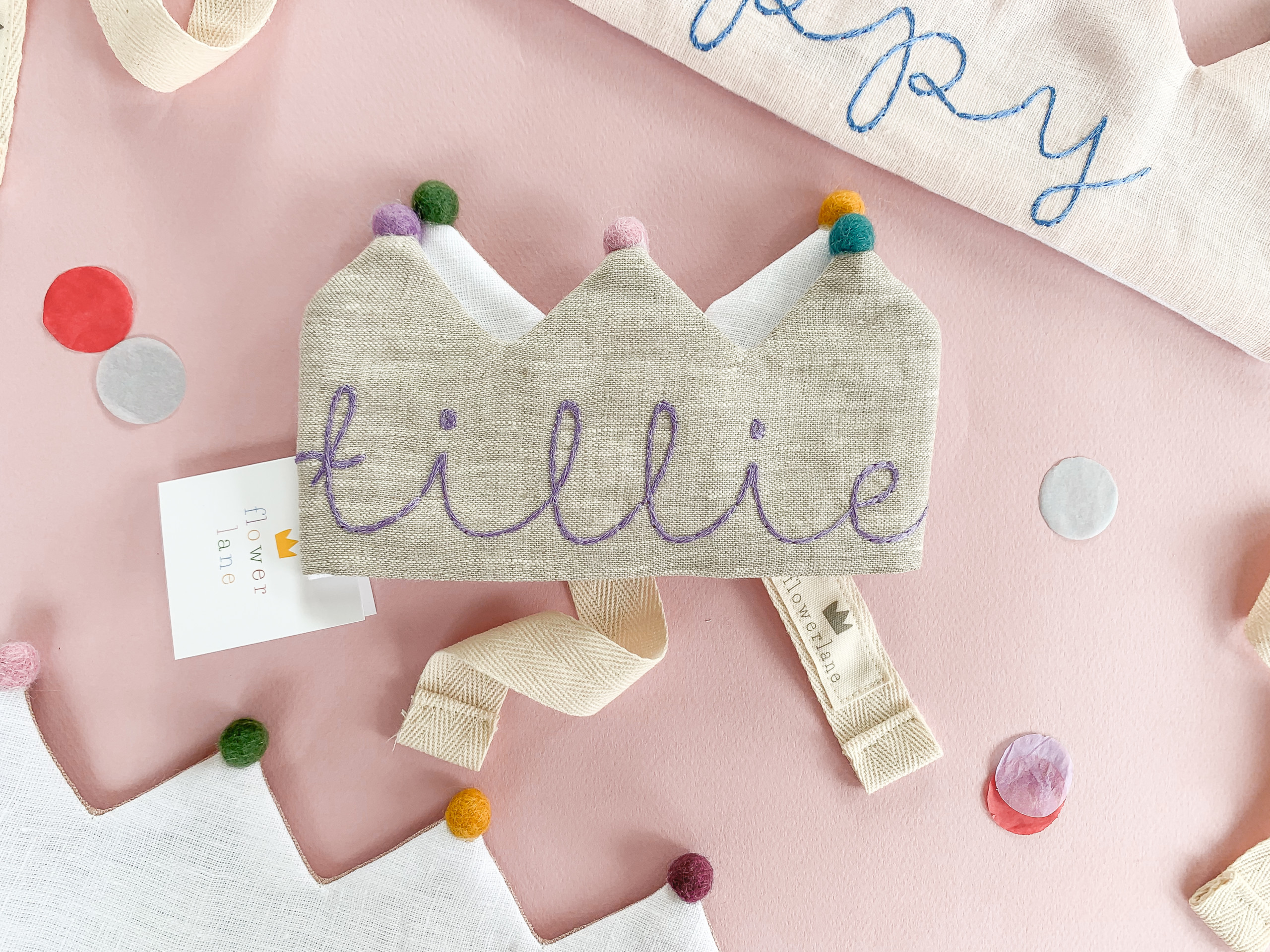 """A grey linen kids birthday crown with rainbow pom poms and the name """"tillie"""" embroidered on it. It's on a pink background."""