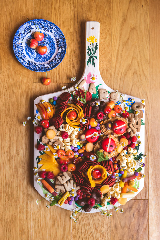a painted charcuterie board loaded with colorful snacks.