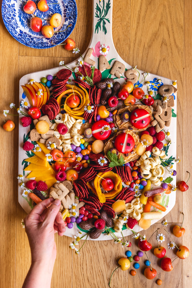 A hand reaches down to a charcuterie board laden with fruits, candies, snacks, veggies, cheese, and crackers.
