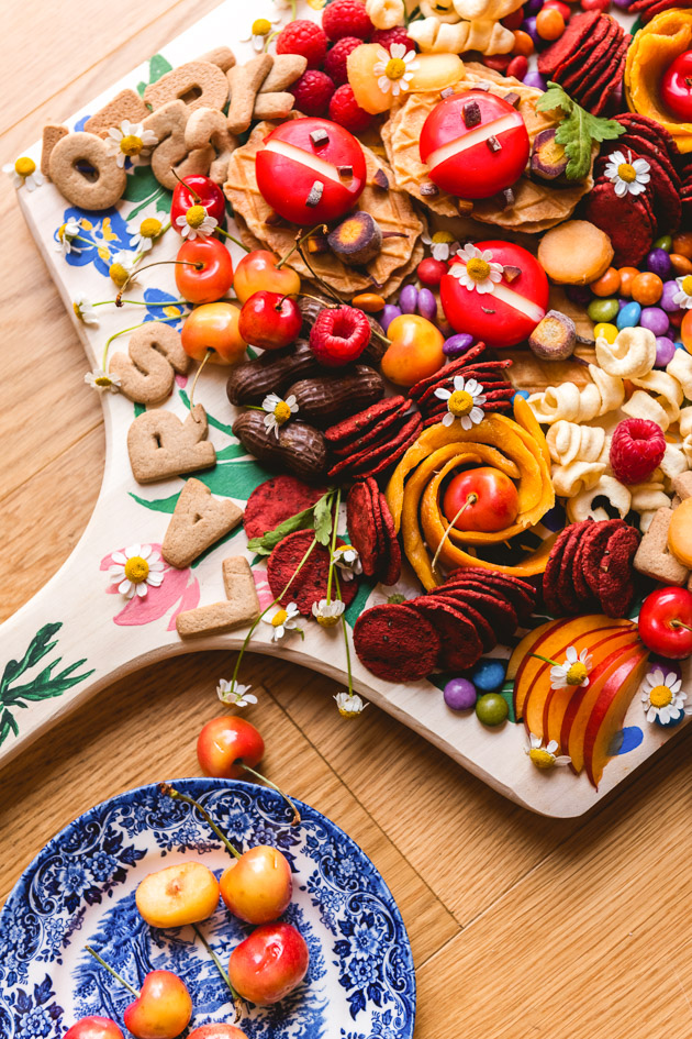 Painted charcuterie board laden with snacks and cookies and fruits and cheeses and treats.