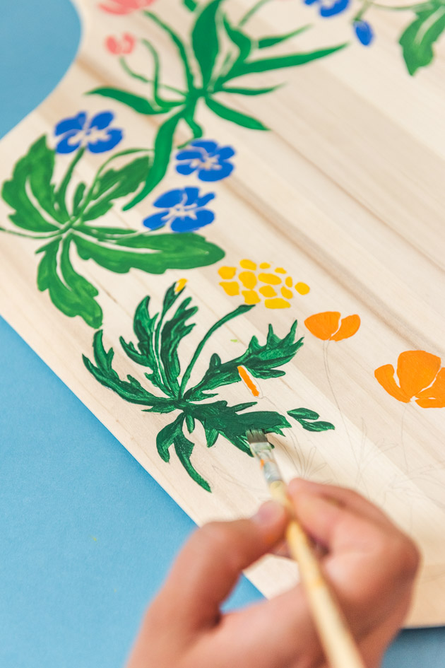 painting a leaf onto a decorative floral painted pizza peel/charcuterie board.