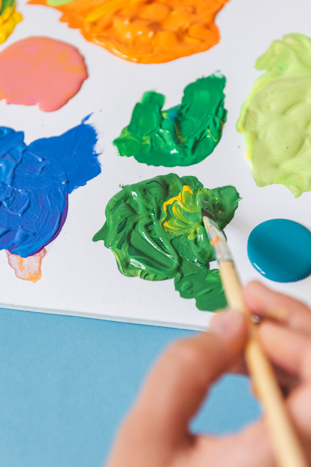 mixing different colors of green, blue, pink, and orange paint.