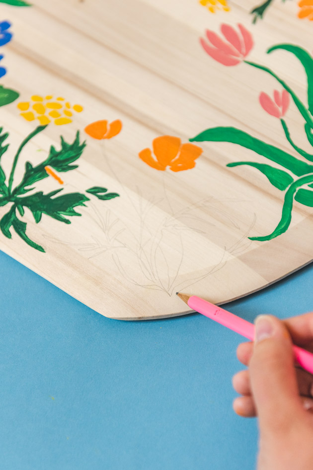 photo of drawing out the design on a wooden pizza peel. The background is blue and the pencil is pink.