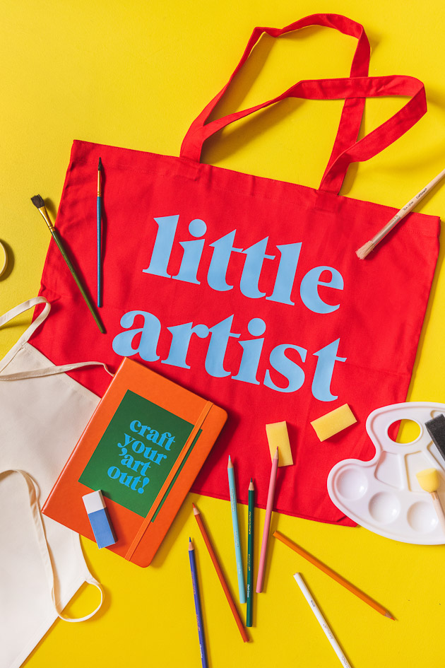 Little Lars art kit, including a red tote, a paint palette, paintbrushes, colored pencils, a sketchbook with a sticker, an eraser, and an apron on a yellow background