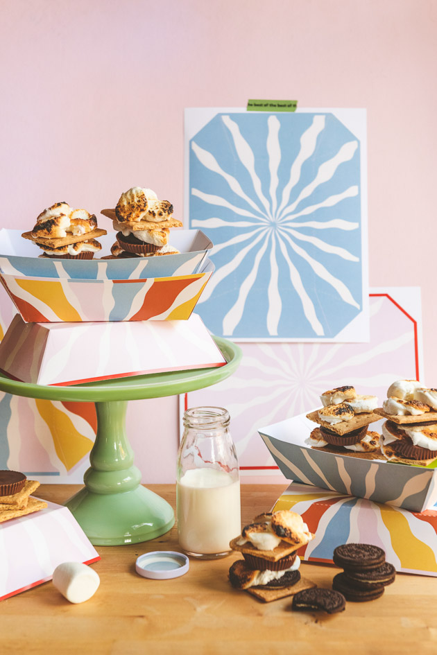 S'mores in colorful paper trays against a pink wall with a jug of milk and some printable templates in the background.
