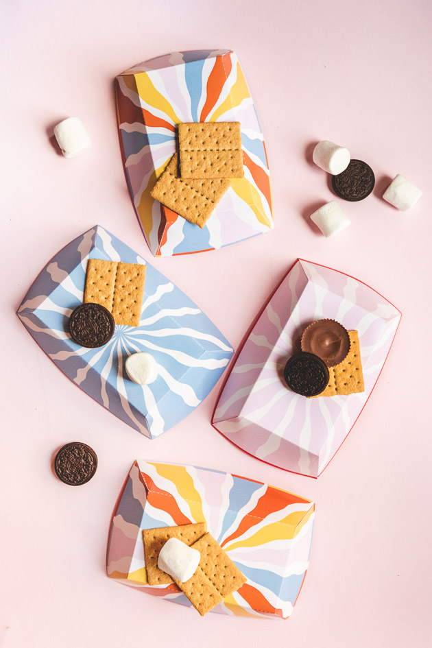flat lay of blue, pink, and multicolored paper s'more trays on a pink background. Graham crackers, marshmallows, oreos, and peanut butter cups are scattered around.