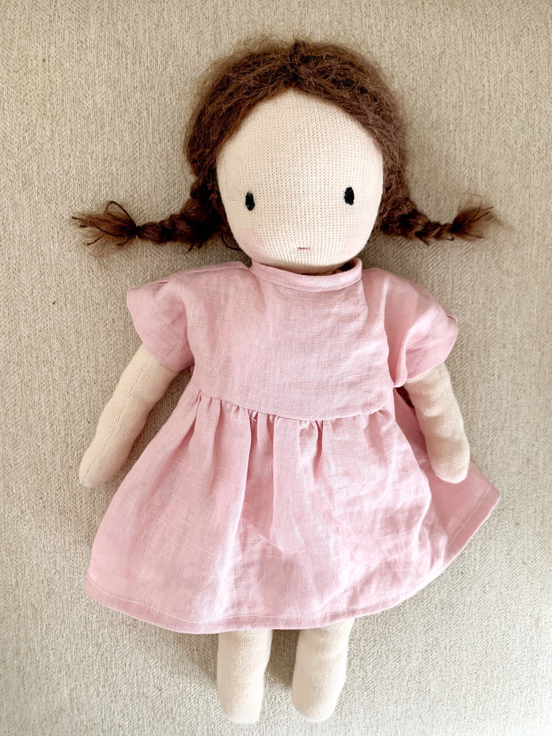 A waldorf-inspired handsewn doll wearing a pink linen dress. The doll has brown braids, pink cheeks, simple features, and is on a beige background.