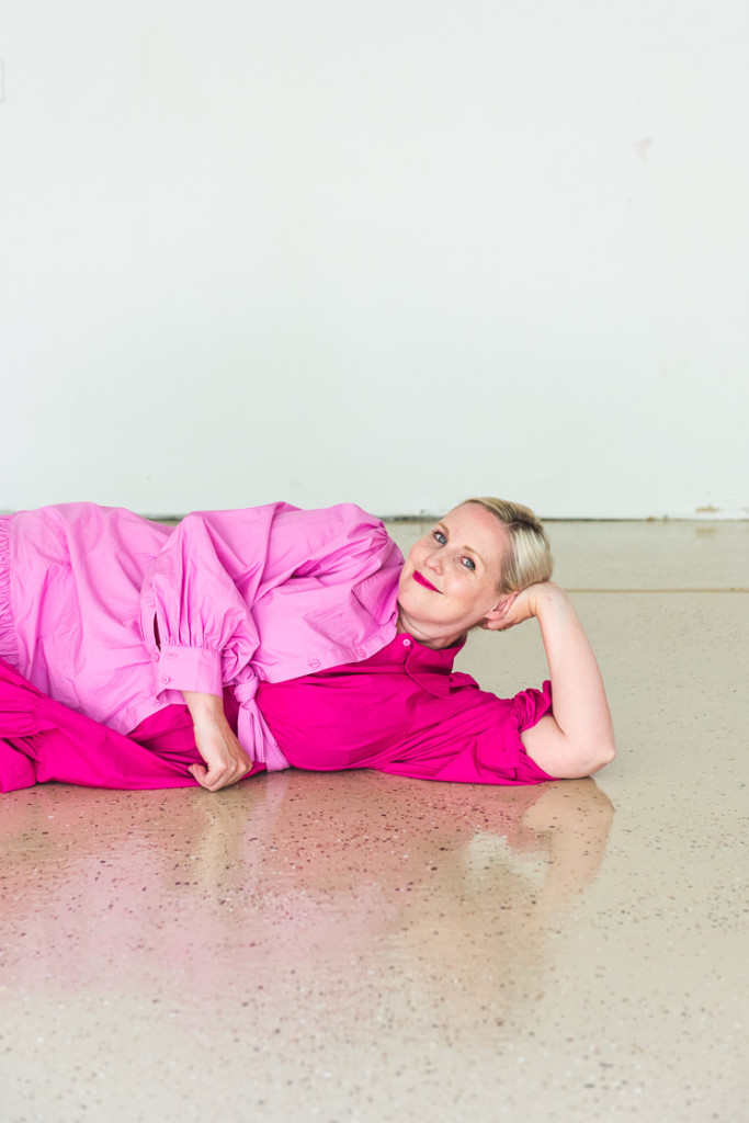 Brittany lies down on the epoxy floor wearing a two-toned pink dress.