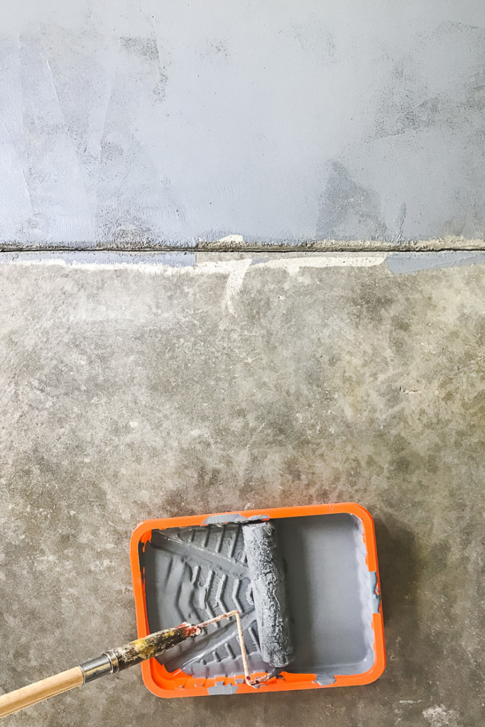 Grey primed cement floor. There's also a paint roller and tray full of primer.